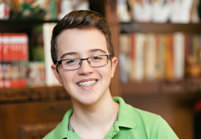 Teenage boy in a green shirt smiles while wearing braces and glasses in a library in Lytle, TX