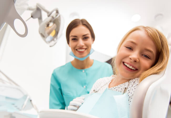 Blonde little girl at the dentist getting a spring cleaning for her teeth