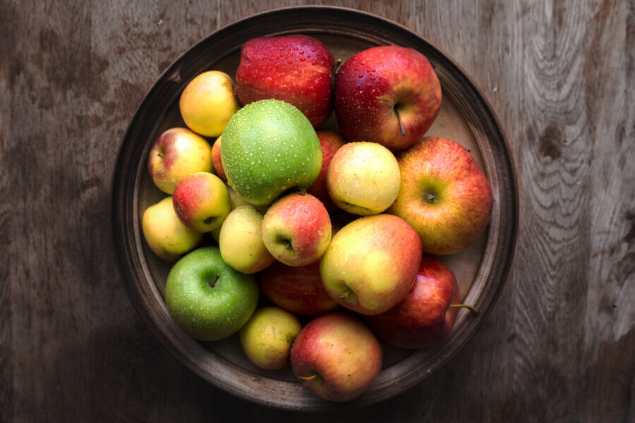 Aerial view of a bowl of whole apples, a healthy snacks for kids teeth