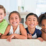 Group of 4 children on a couch smile with dental sealants in Lytle, TX