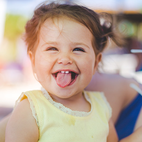 toddler girl sticking out her tongue
