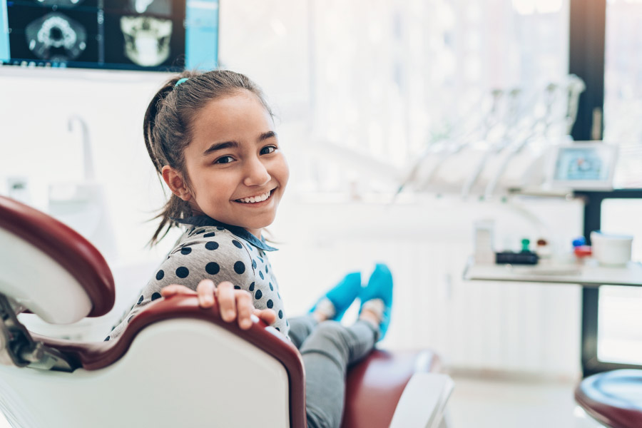 Brunette girl smiles while sitting in the dentist chair at her pediatric dentist in Lytle, TX