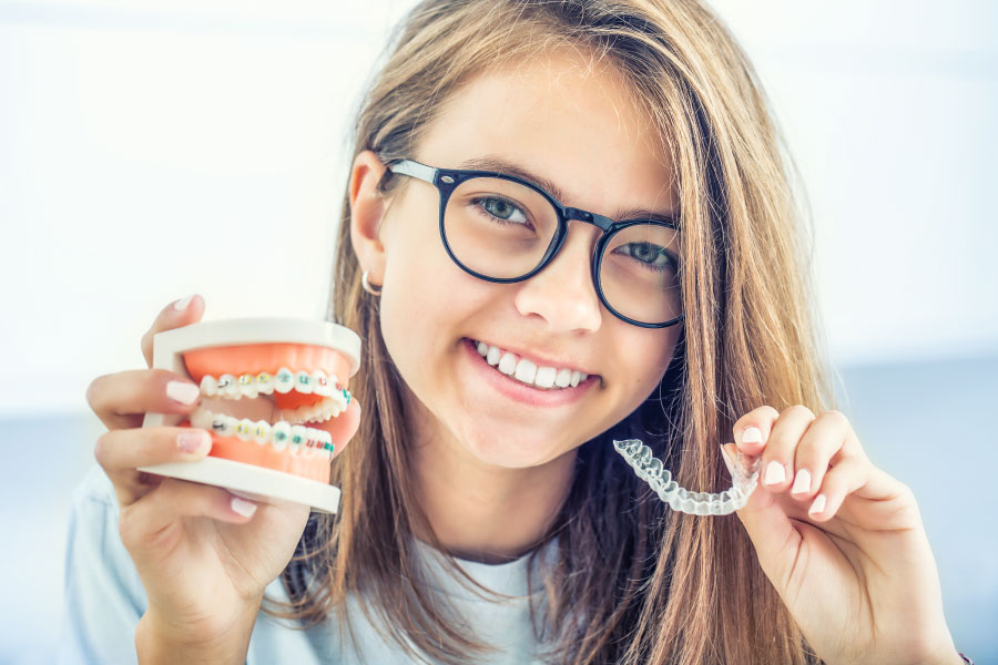 Brunette teenager holds up braces vs Invisalign aligners to compare which is right for her