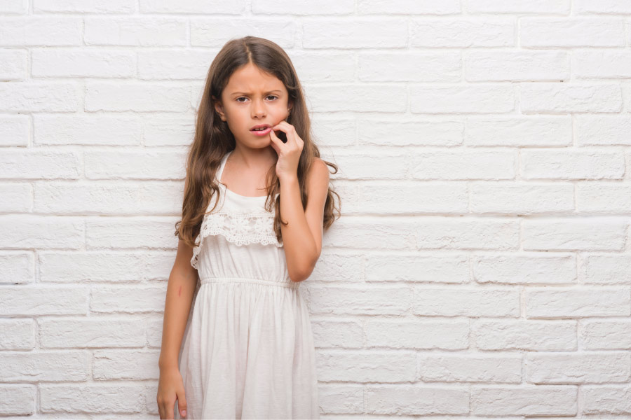 Brunette little girl cringes in pain and touches her cheek because she needs root canal treatment
