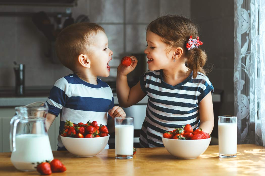 A little boy and girl are feeding each other strawberries for a big bowl next to a glass of milk.