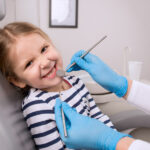 Blonde girl in a striped shirt smiles in the dentist chair while her dentist checks her teeth