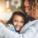 Curly-haired mom and her child with dental sealants smile as they snuggle