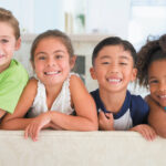 Group of children smiling after receiving dental sealants at Tots to Teens Pediatric Dentistry & Orthodontics in Lytle, TX
